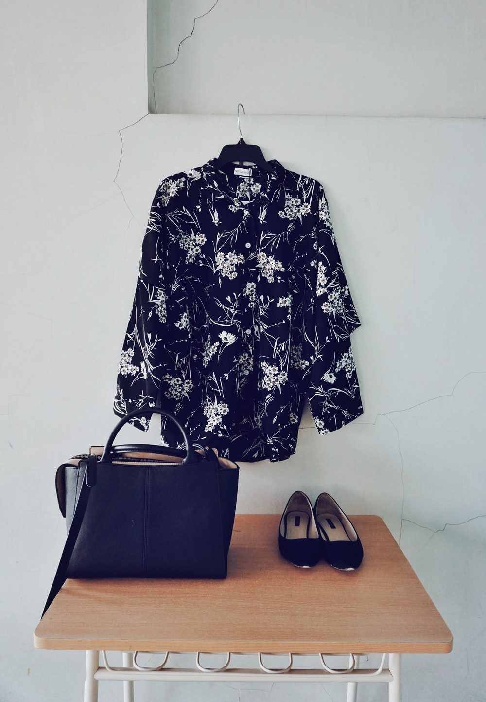 black and white floral sport shirt hanging beside black leather 2-way tote bag and ballet flats