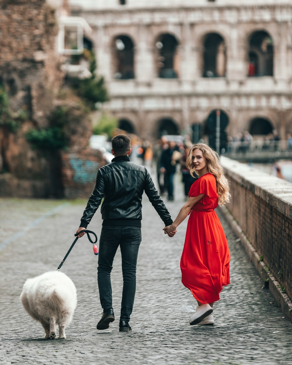 man wearing black jacket holding leash of dog and woman hand