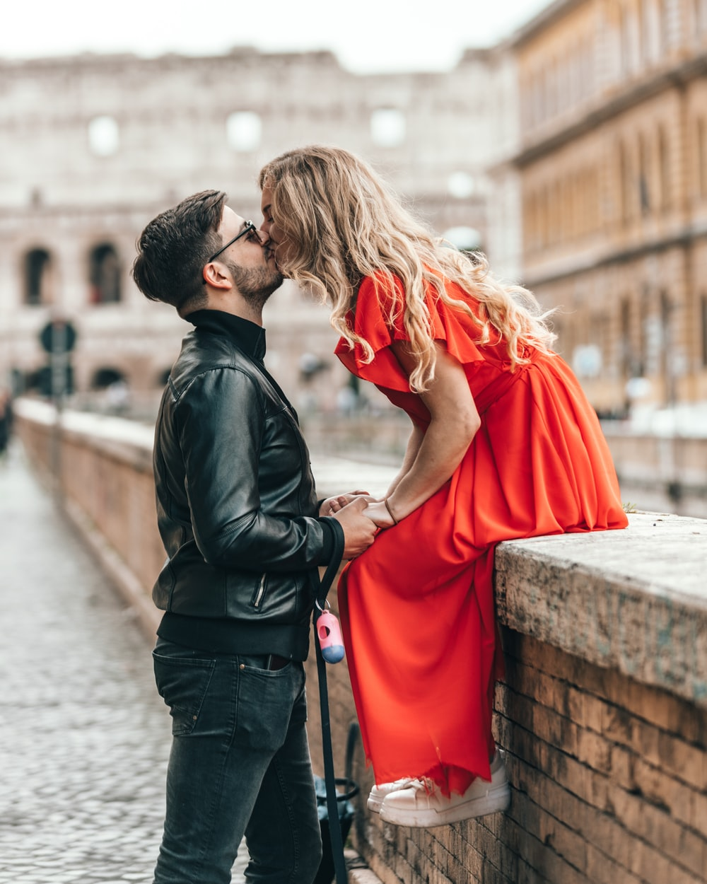 man standing and kissing woman sitting on concrete wall