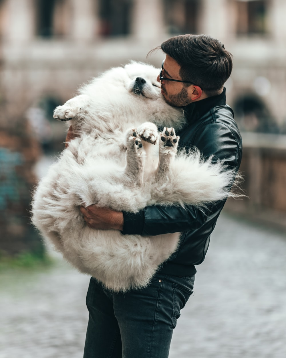 man in eyeglasses and black jacket carrying white dog