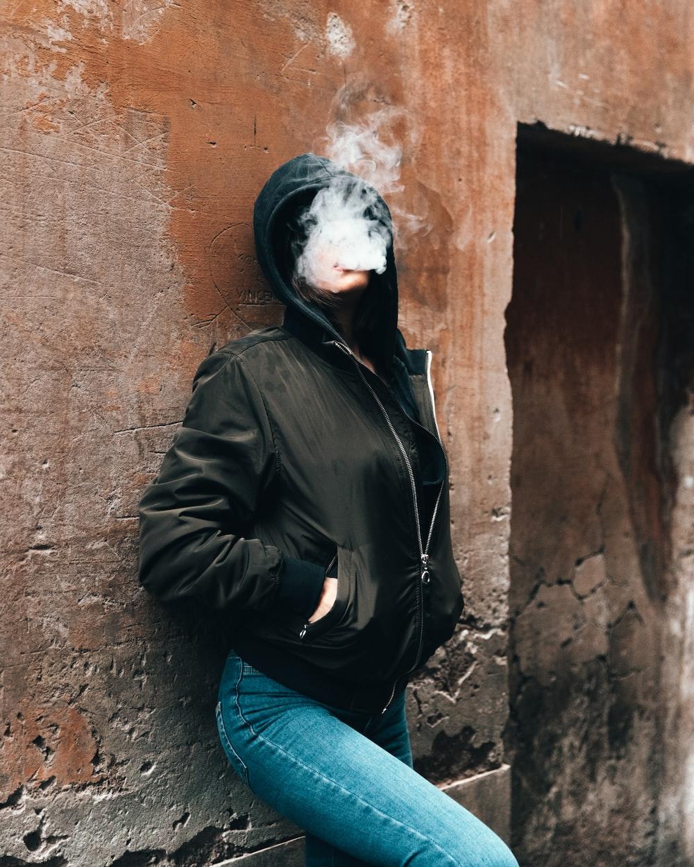 mulher fumando enquanto encostada na parede