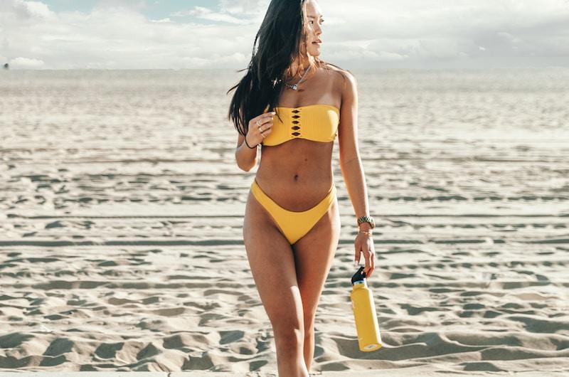 standing woman wearing yellow bikini holding yellow bottle