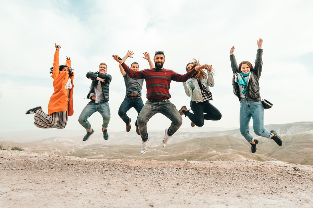 six group of people jumping on hill
