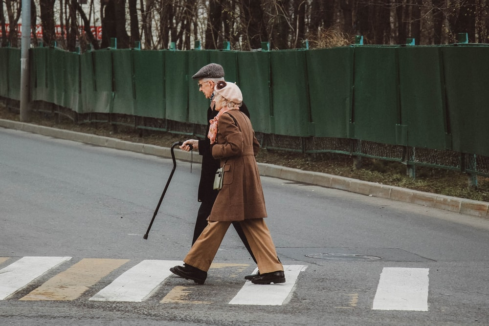 man and woman walking on pedestrian line during daytime