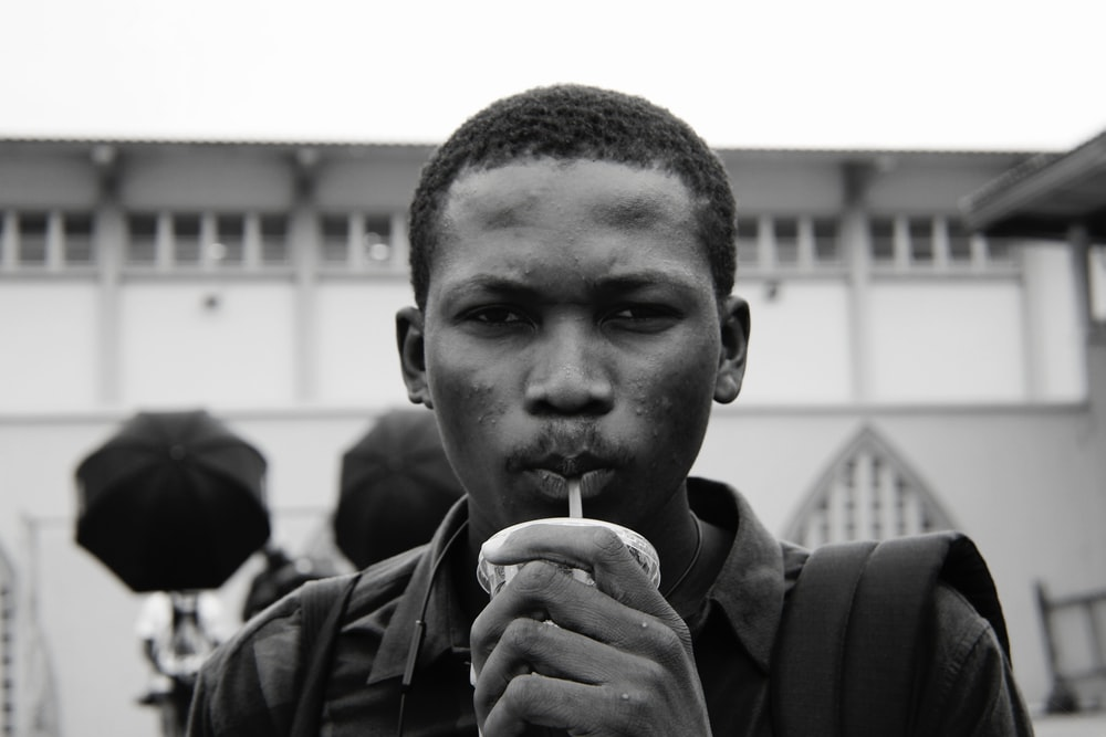 grayscale photography of man sipping on straw