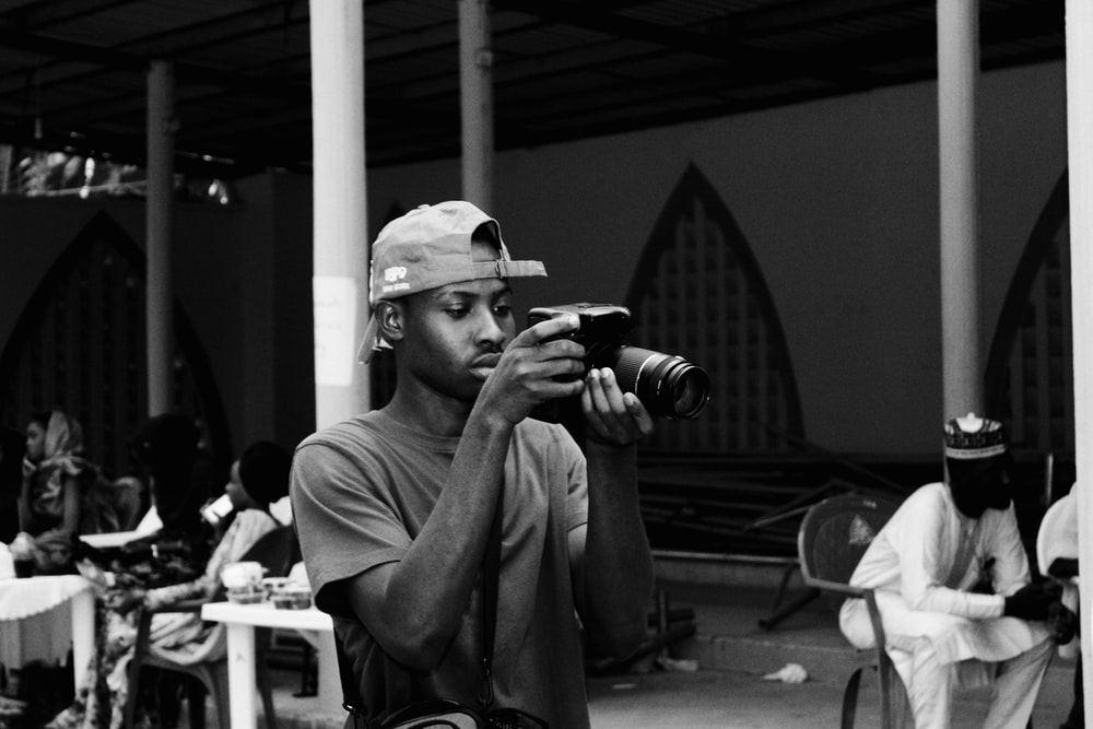 grayscale photography of man using DSLR camera