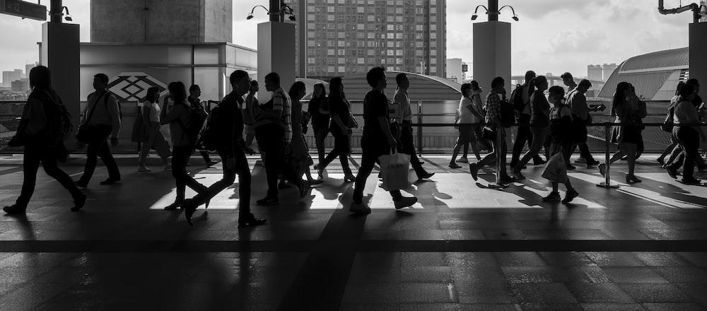 grayscale photography of people walking on floor