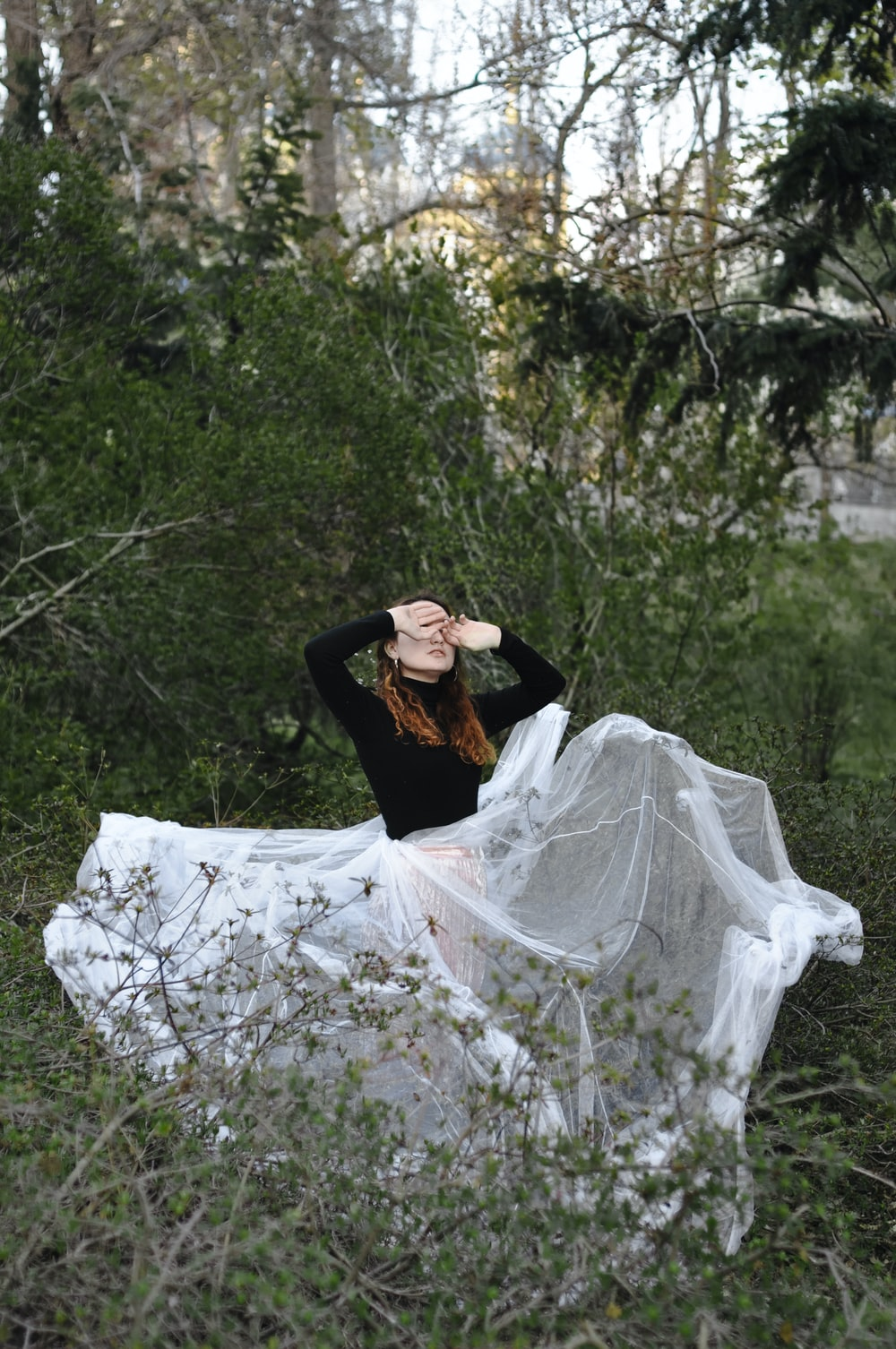 woman in white and black dress sitting on forest