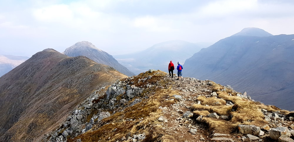 two person walking on top of mountain
