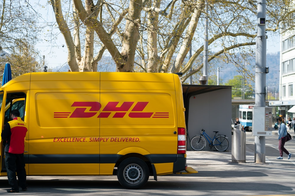 man standing in front of DHL truck door