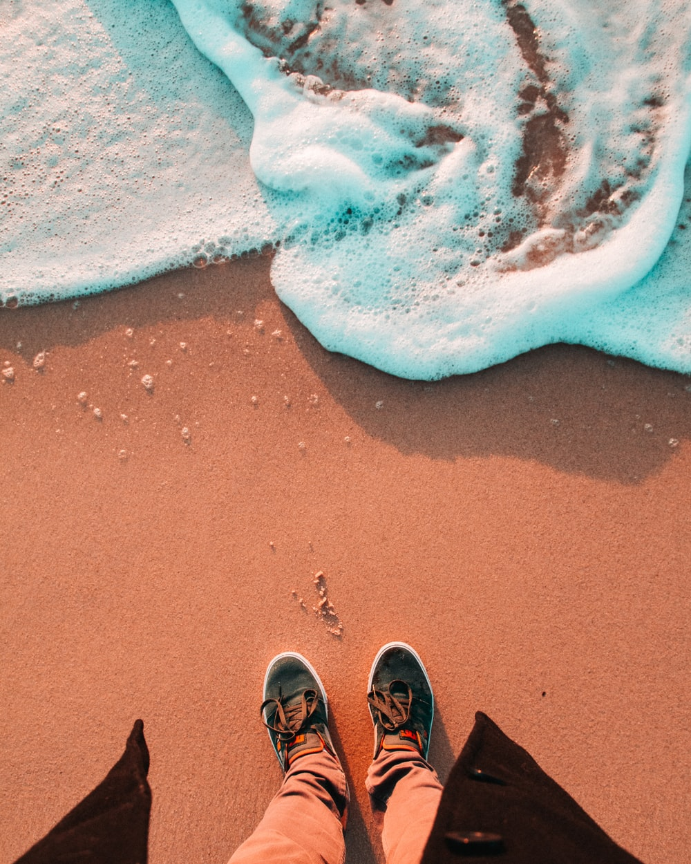 person wearing black shoes standing in front of seashore waves