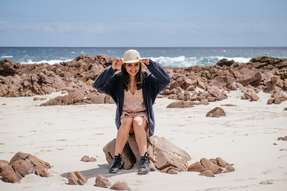 woman in blue jacket sitting on rock by the beach while holding sun hat