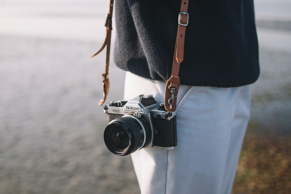 person wearing black top and white bottoms holding black camera