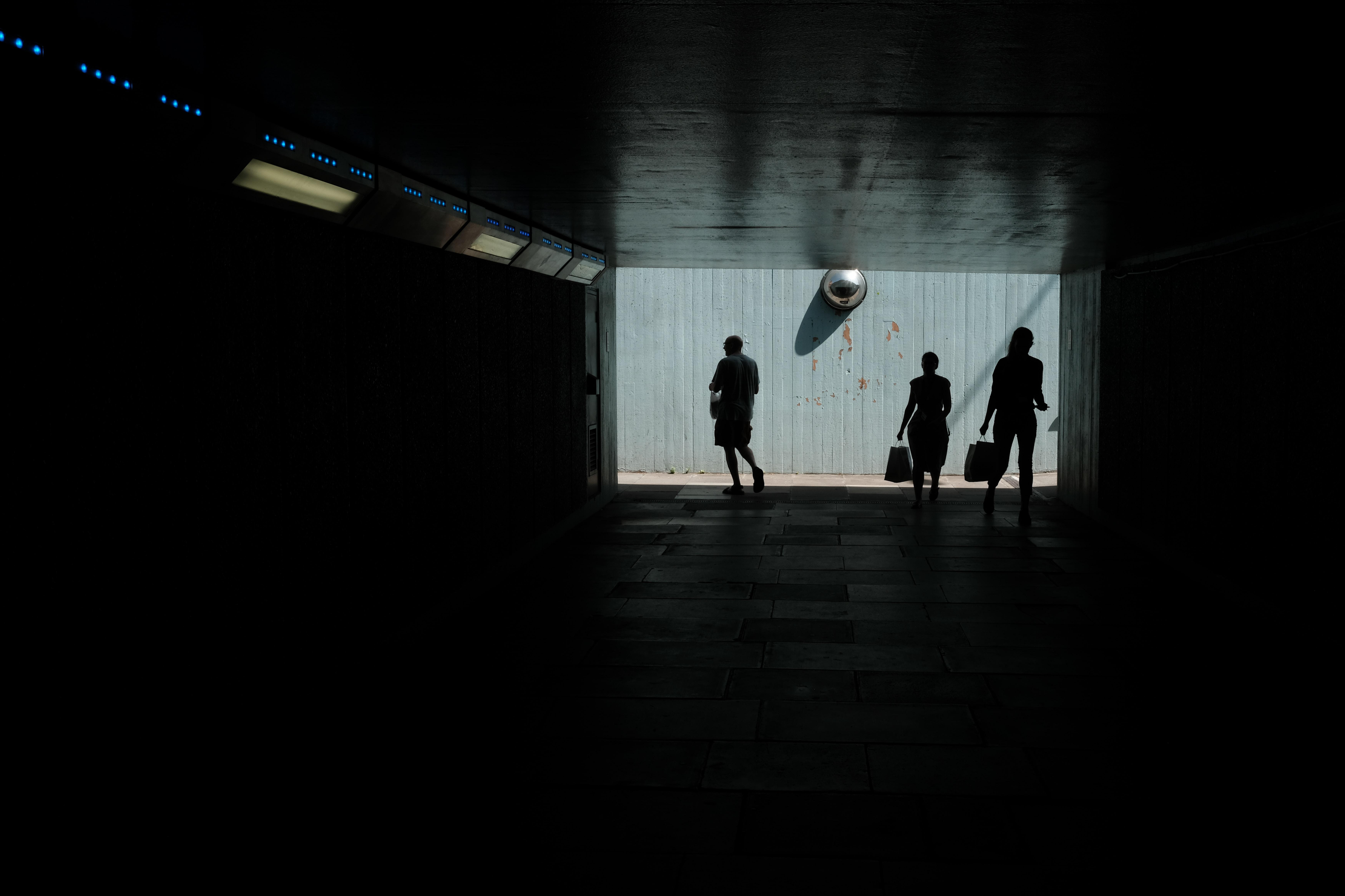 three persons walking through dark pathway