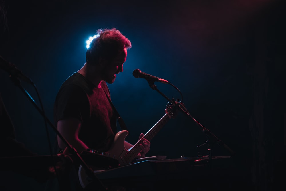 man playing electric guitar performing on stage
