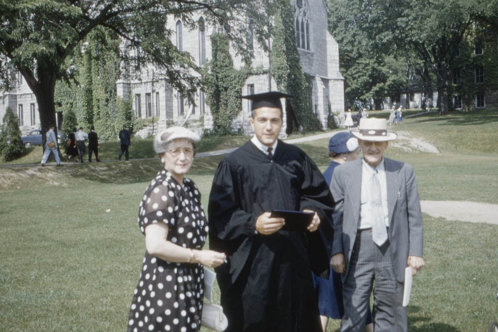 man wearing academic suit standing beside man and woman