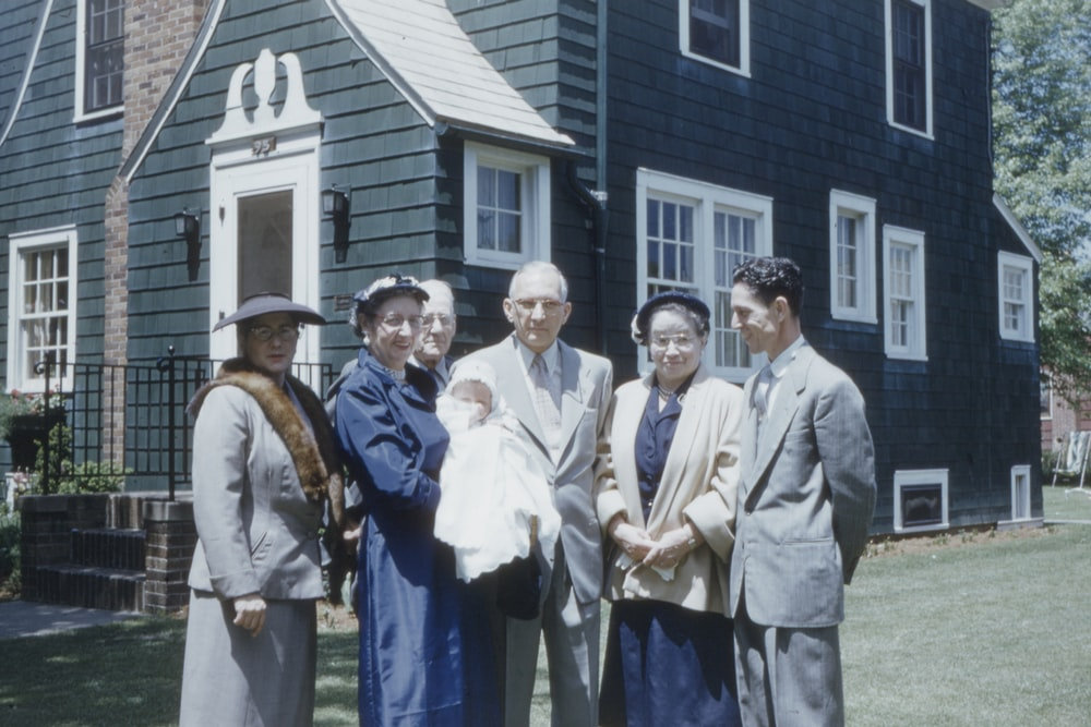group of people standing near house