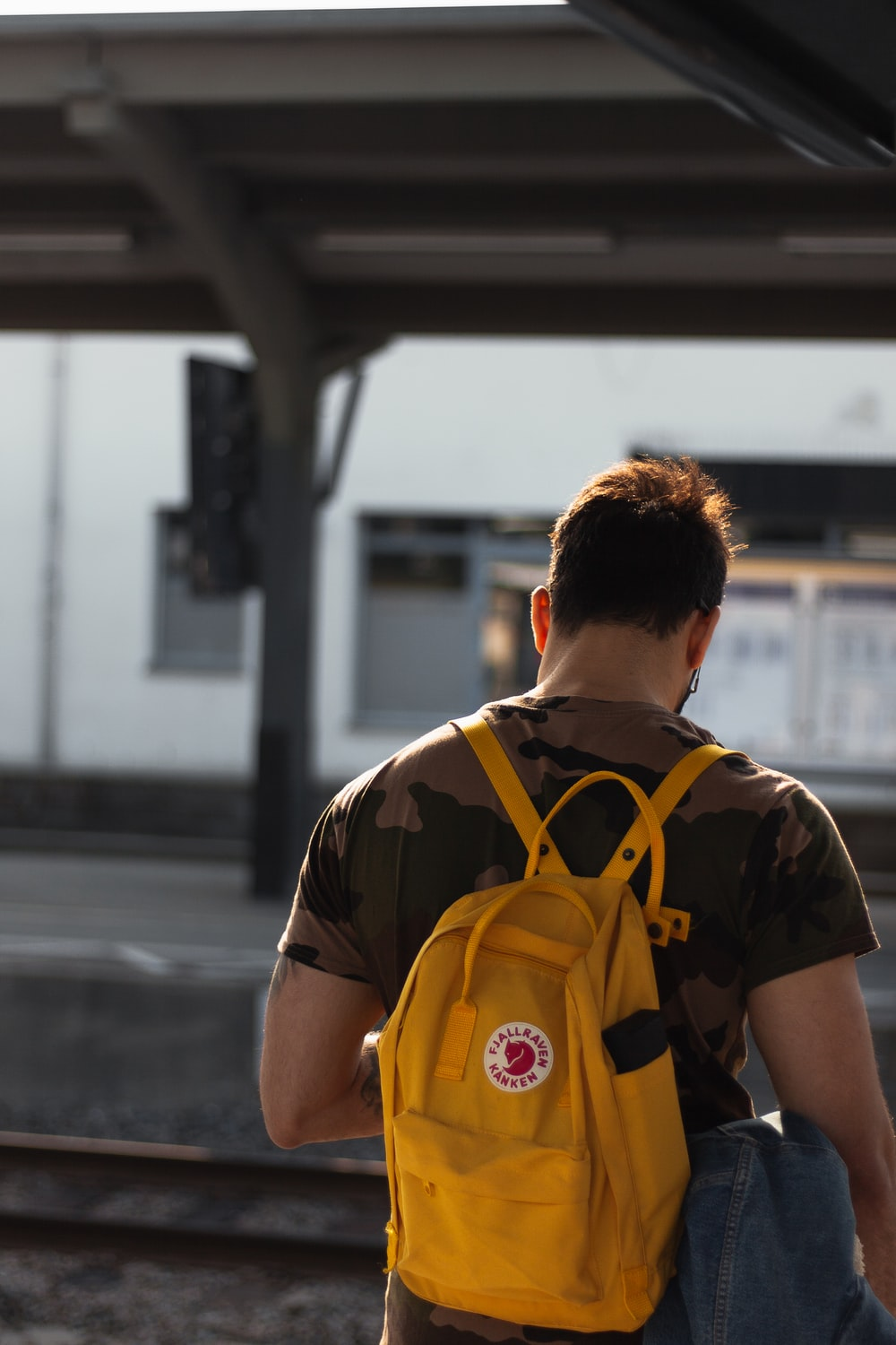 man carrying yellow backpack in train station