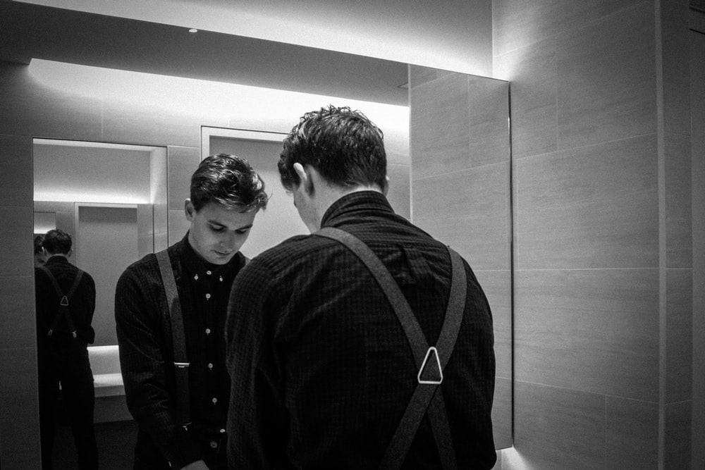 grayscale photography of man standing front of mirror