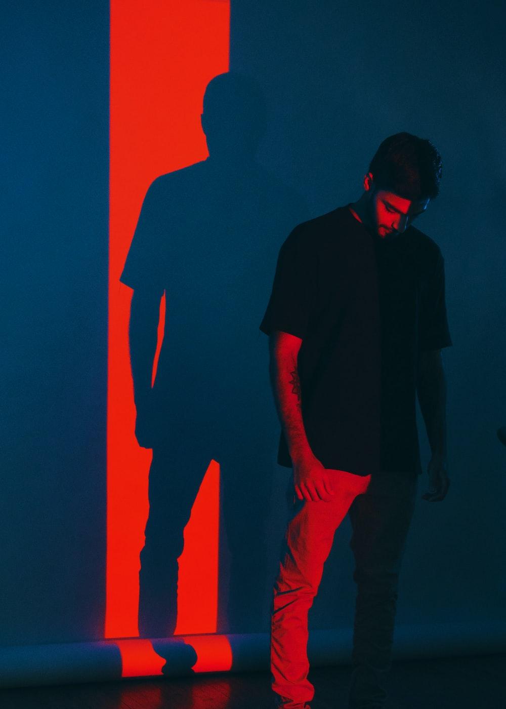 man wearing black shirt standing near wall