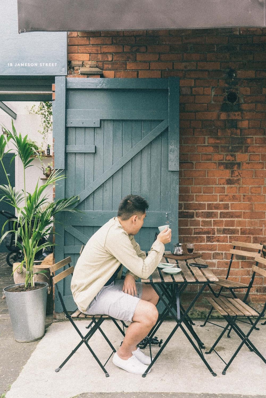 man sitting on chair holding mug