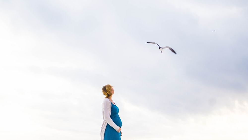 woman in blue and white dress standing and looking at flying bird