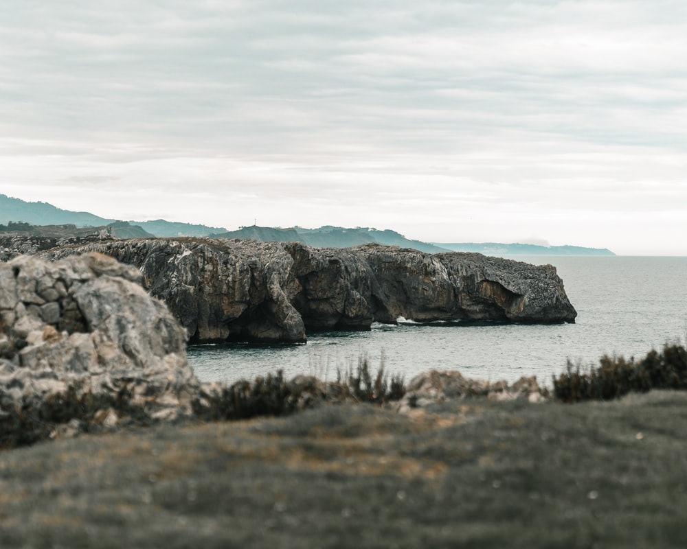 gray rock formation on sea at daytime