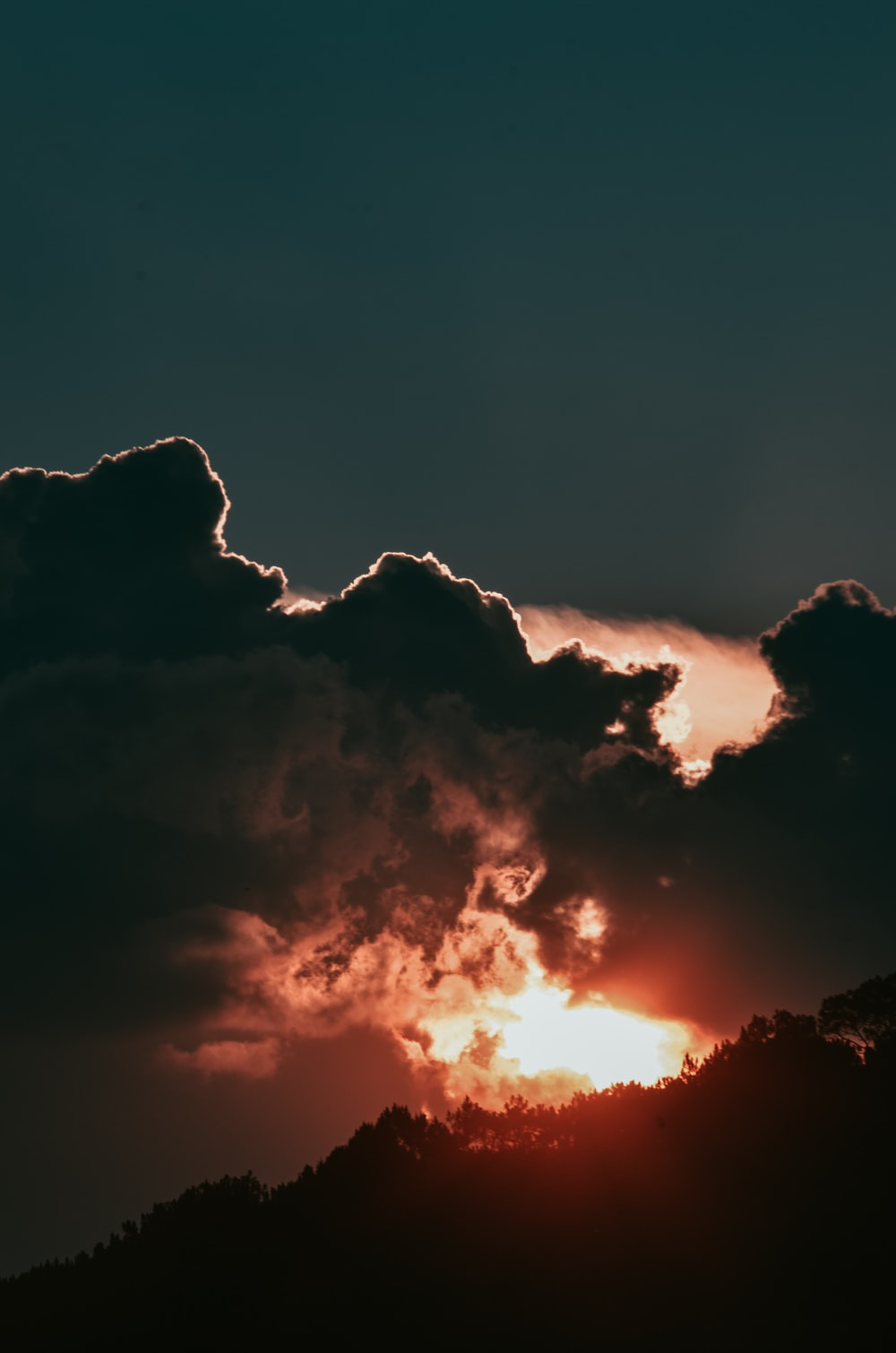 silhouette of mountain under cloudy sky during golden hour