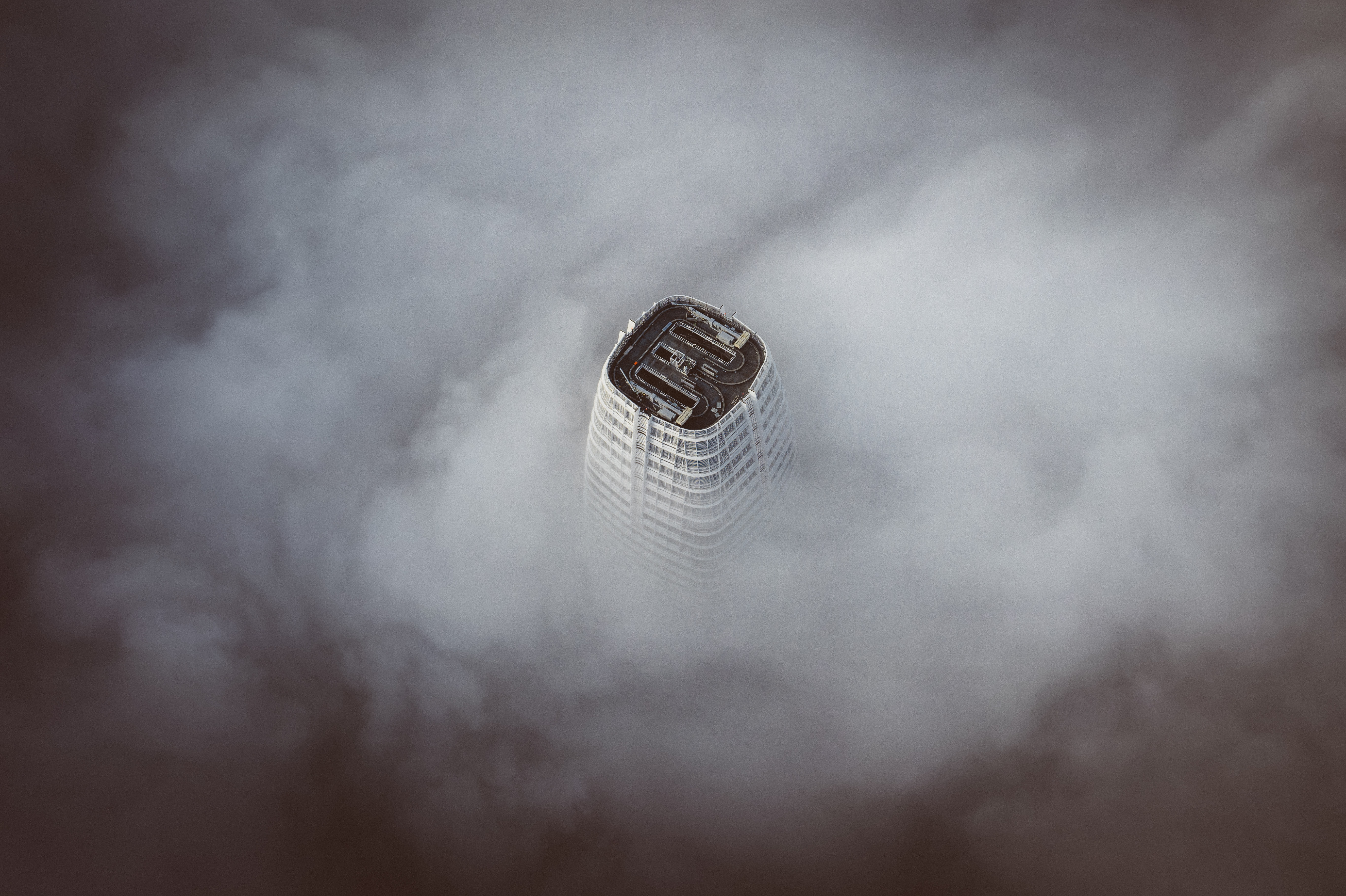 white concrete building surrounded by clouds