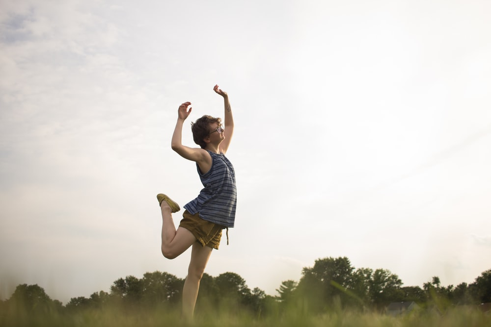 person standing raising right leg as well as both hands