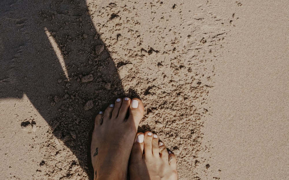 person stepping on sand