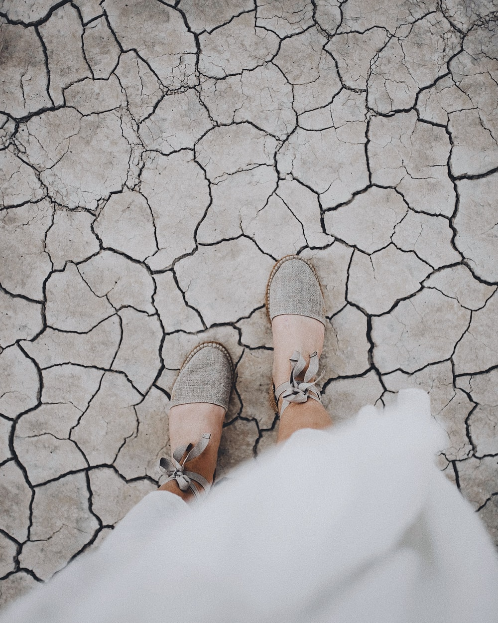 woman in gray flats standing on dried field