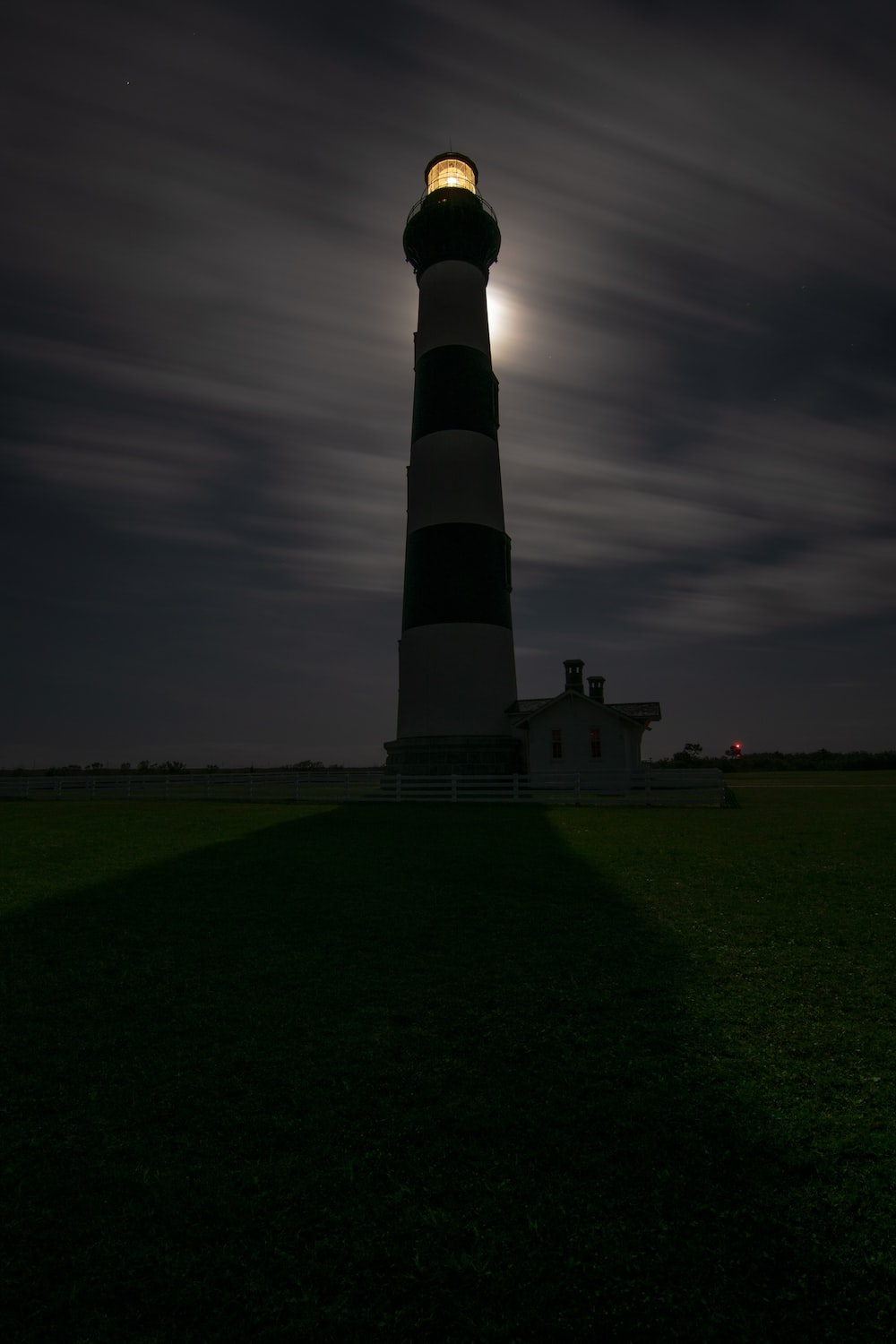 lighthouse under cloudy sky at night