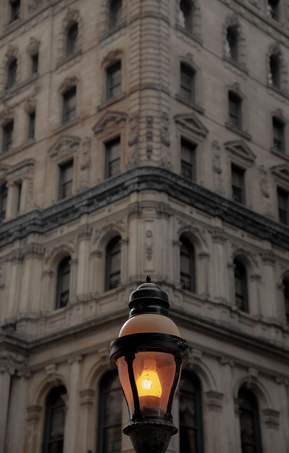 street lamp near white concrete building during daytime