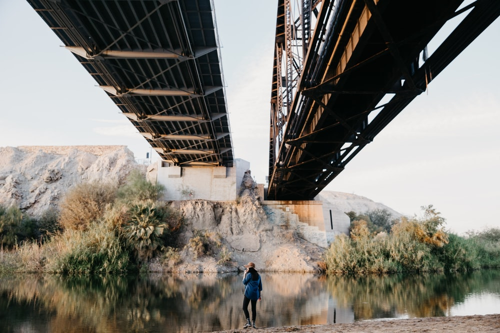 person standing under brown bridge