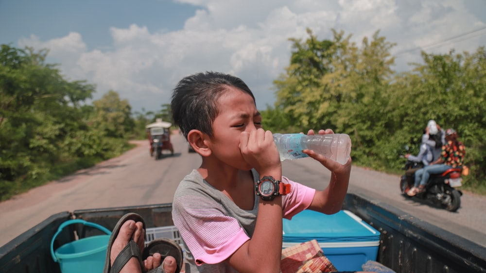person drinking on bottled water at pickup truck during daytime