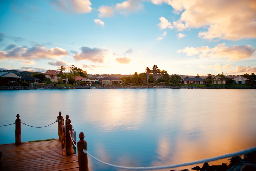 brown wooden dock with houses background