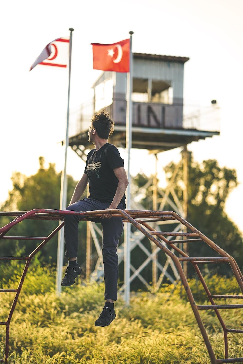 man sitting on red metal monkey bar during daytime