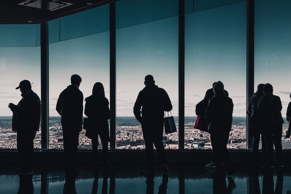 silhouette of people standing near glass wall