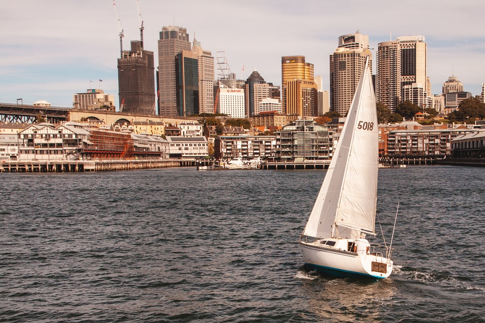 white sailboat on rippling water near buildings