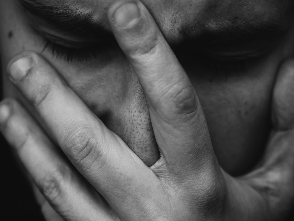 grayscale photo of person placing hand on face