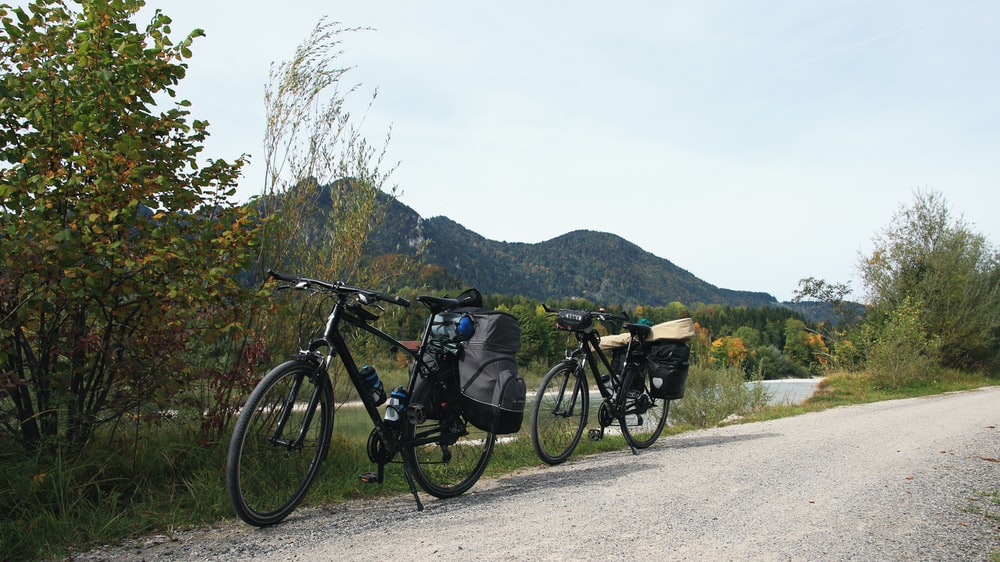 two mountain bikes parked by the road overlooking mountain during daytime