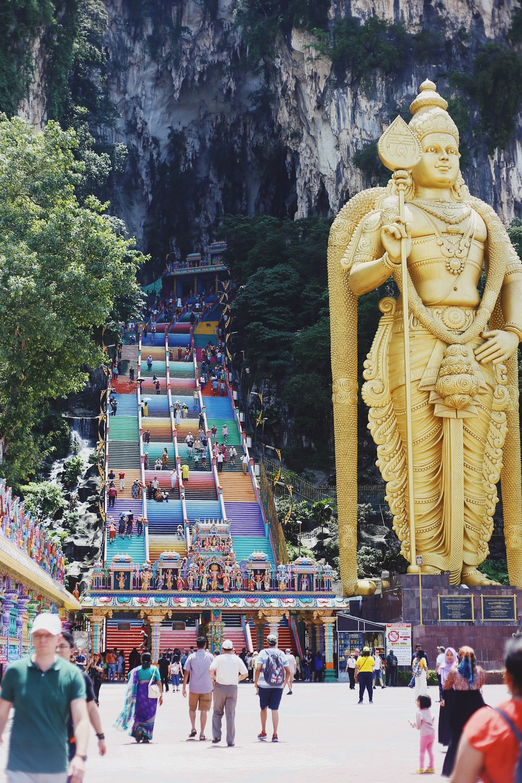 group of people walking near Hindu deity statue