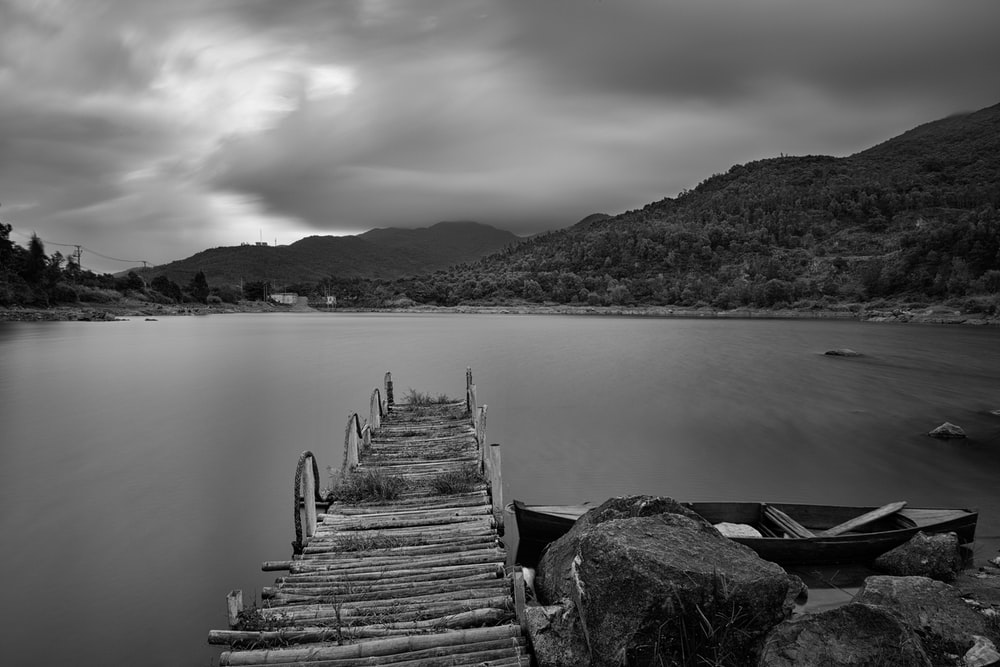 grayscale photo of dock and lake