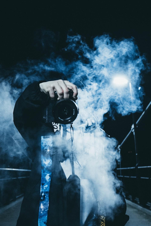 person using DSLR camera near white smoke