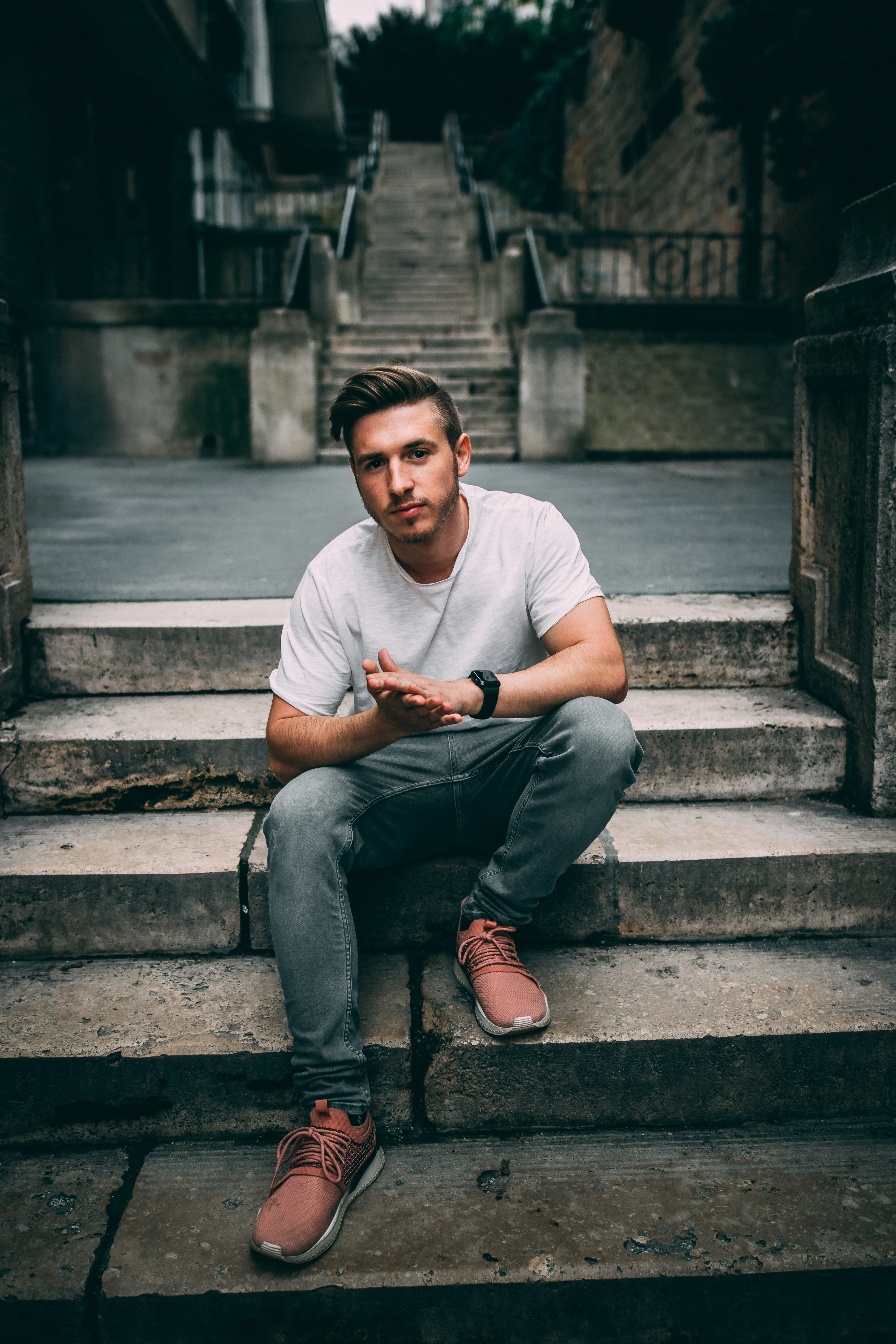 unknown celebrity sitting on concrete step outdoors