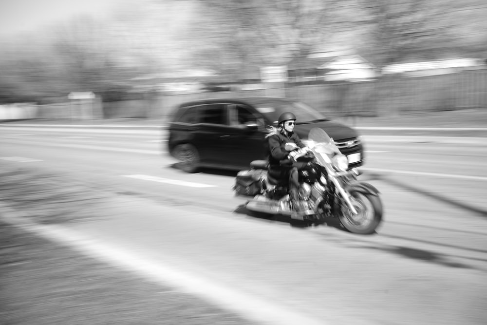 motorcyclist on road by car