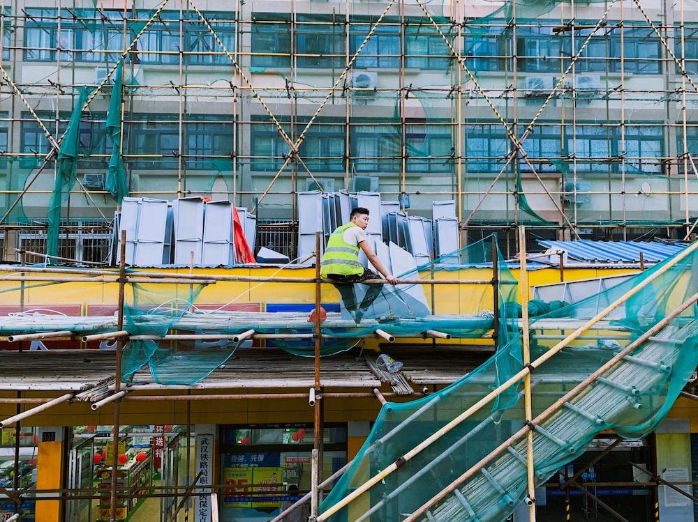 man sitting on scaffolding