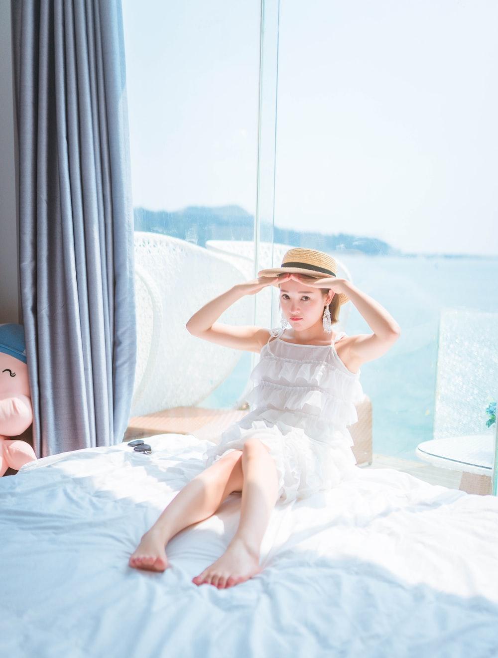 woman wearing white sleeveless dress on bed