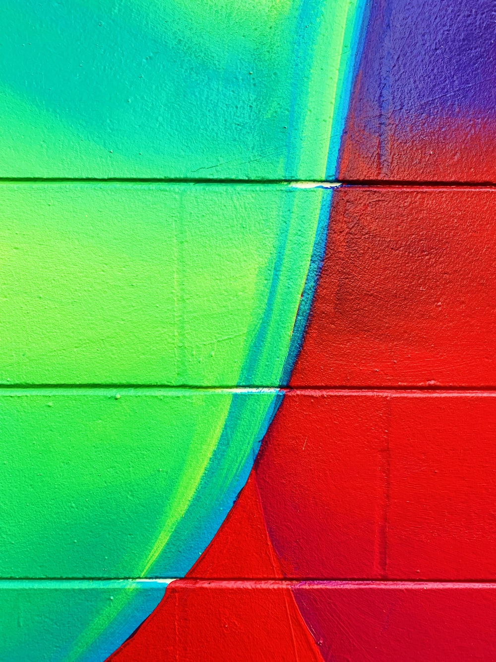 green, blue, and red painted brick wall